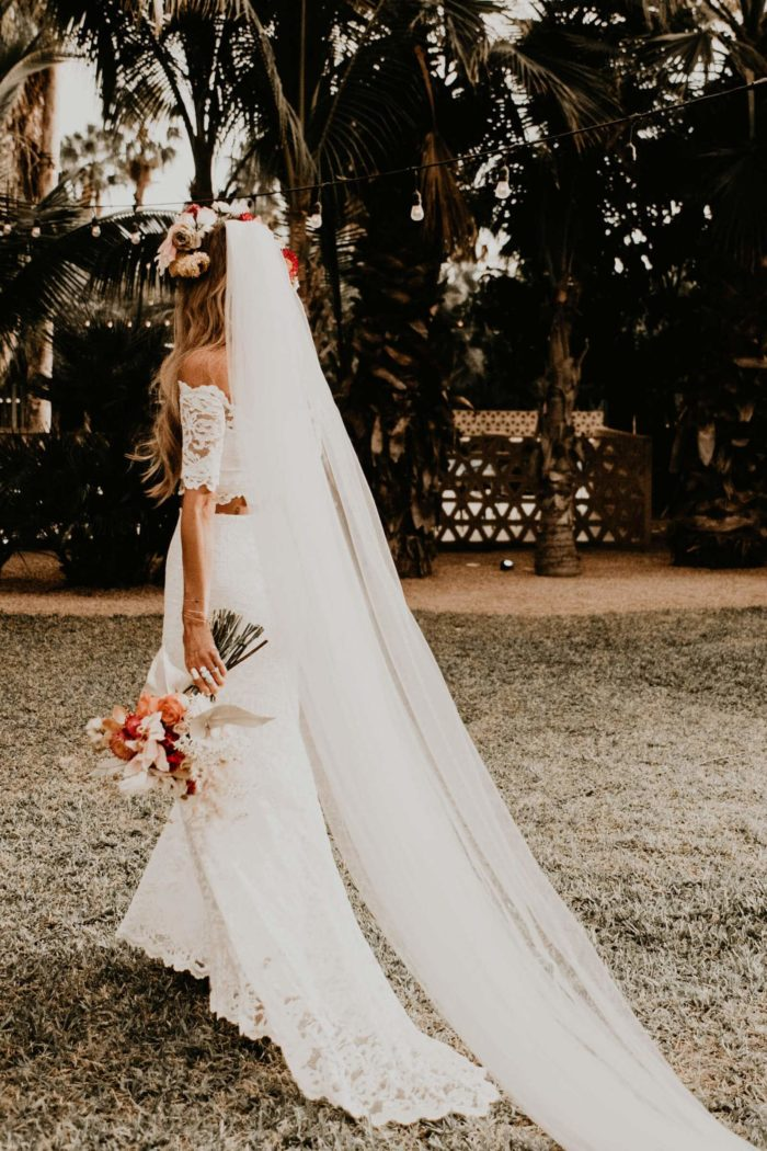 Back shot of bride wearing Grace Loves Lace Everly Gown holding bouquet
