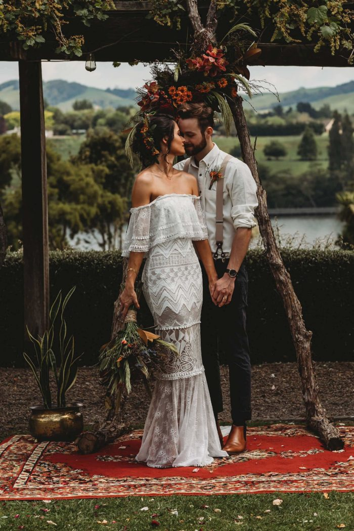 Brunette bride wearing Grace Loves Lace Emanuela Gown holding hands with groom while kissing
