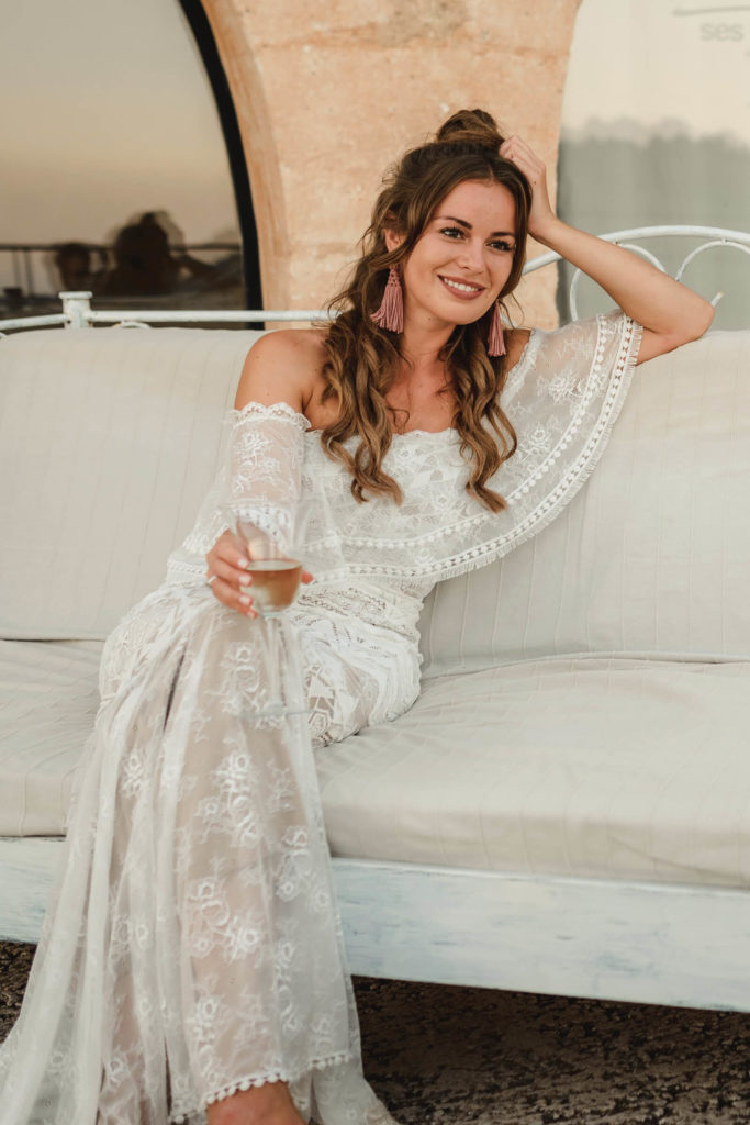Brunette bride wearing Grace Loves Lace Emanuela Gown sitting on a white sofa holding a champagne glass