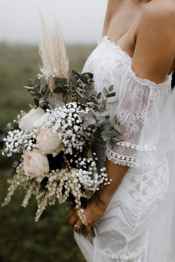 Close-up of bride wearing Grace Loves Lace Emanuela Gown holding bouquet