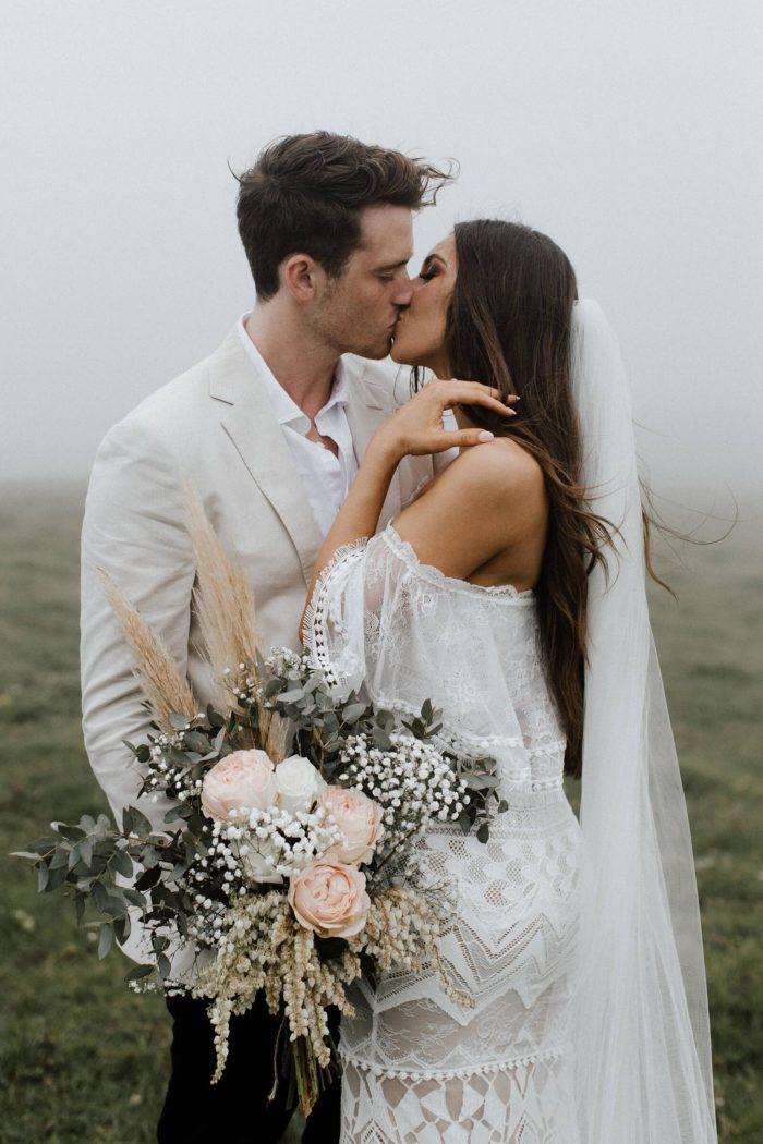 Brunette bride wearing Grace Loves Lace Emanuela Gown and veil kissing groom