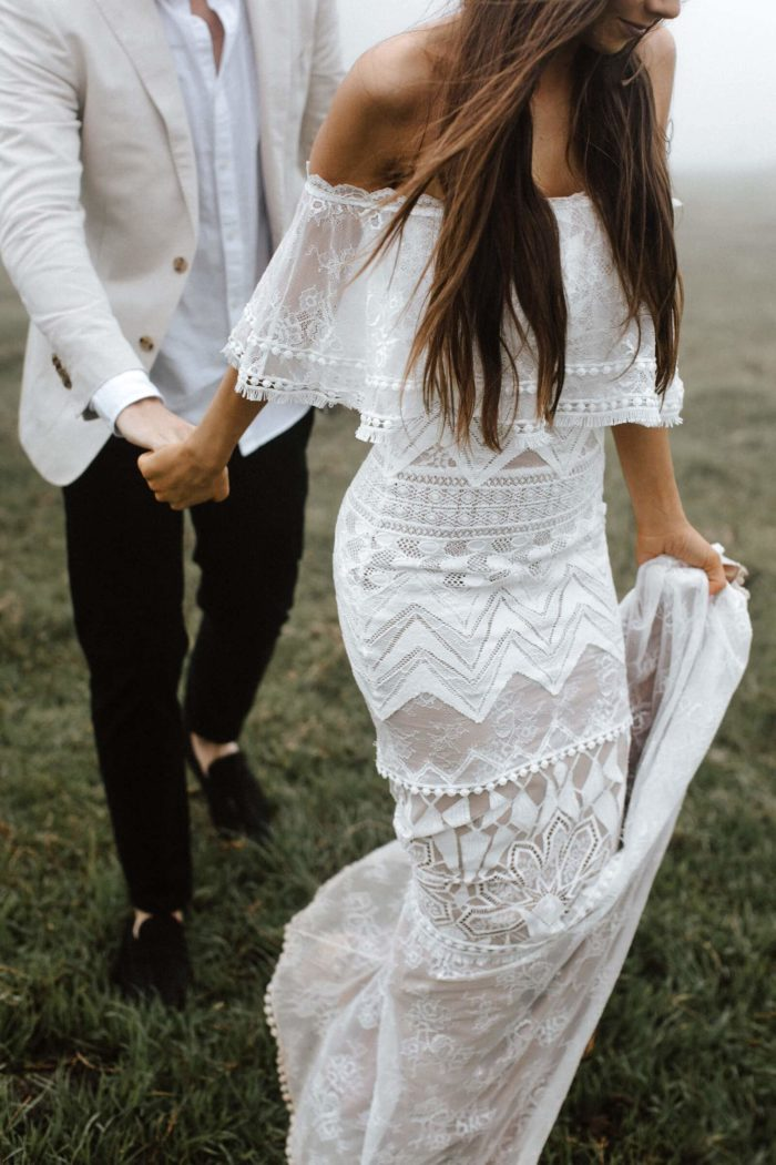 Brunette bride wearing Grace Loves Lace Emanuela Gown holding hands with groom