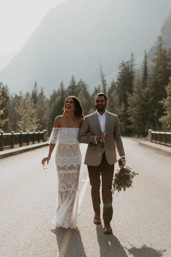 Brunette bride wearing Grace Loves Lace Emanuela Gown walking down road with groom holding champagne glass