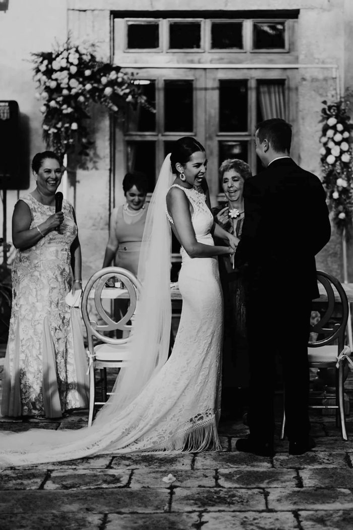 Black and white shot of bride wearing Grace Loves Lace Edie Gown standing with groom and family