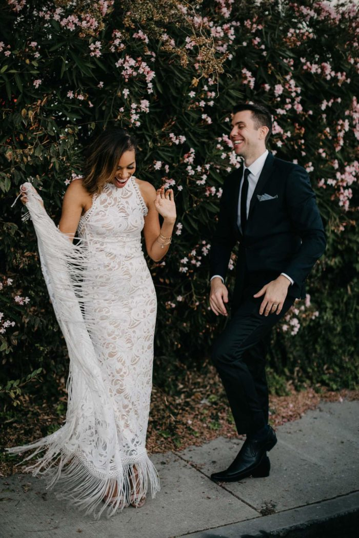 Brunette bride wearing Grace Loves Lace Edie Gown holding train in one hand standing with groom