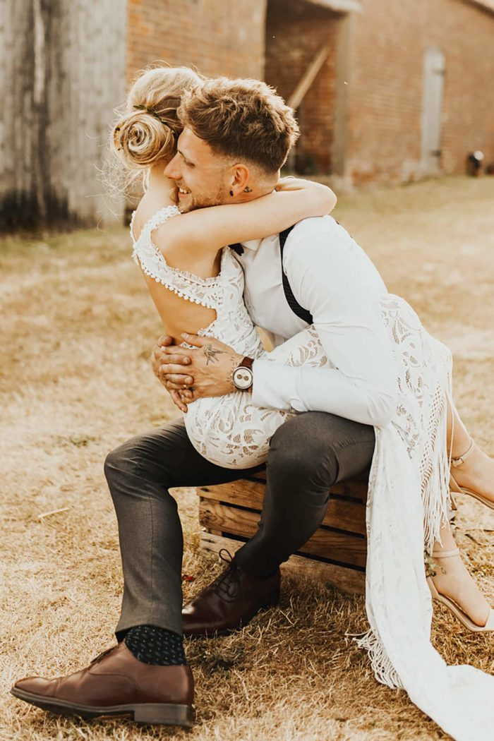 Blonde bride wearing Grace Loves Lace Edie Gown being held by groom sitting down on crate