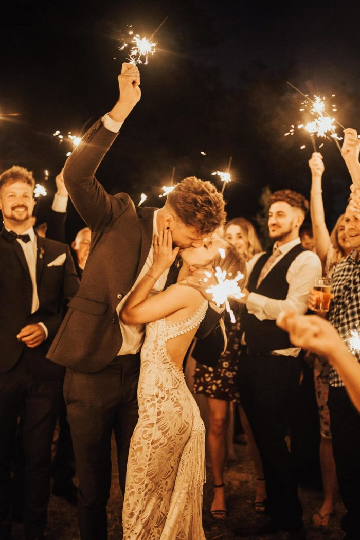 Blonde bride wearing Grace Loves Lace Edie Gown kissing groom at night surrounded by people holding sparklers