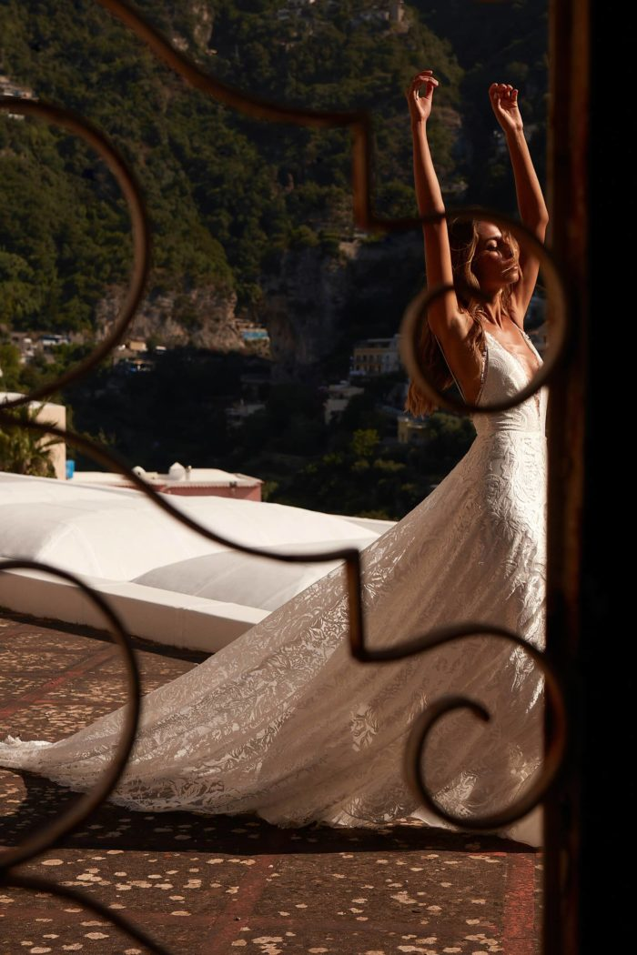 Brunette bride wearing Grace Loves Lace Darling Gown with arms above head