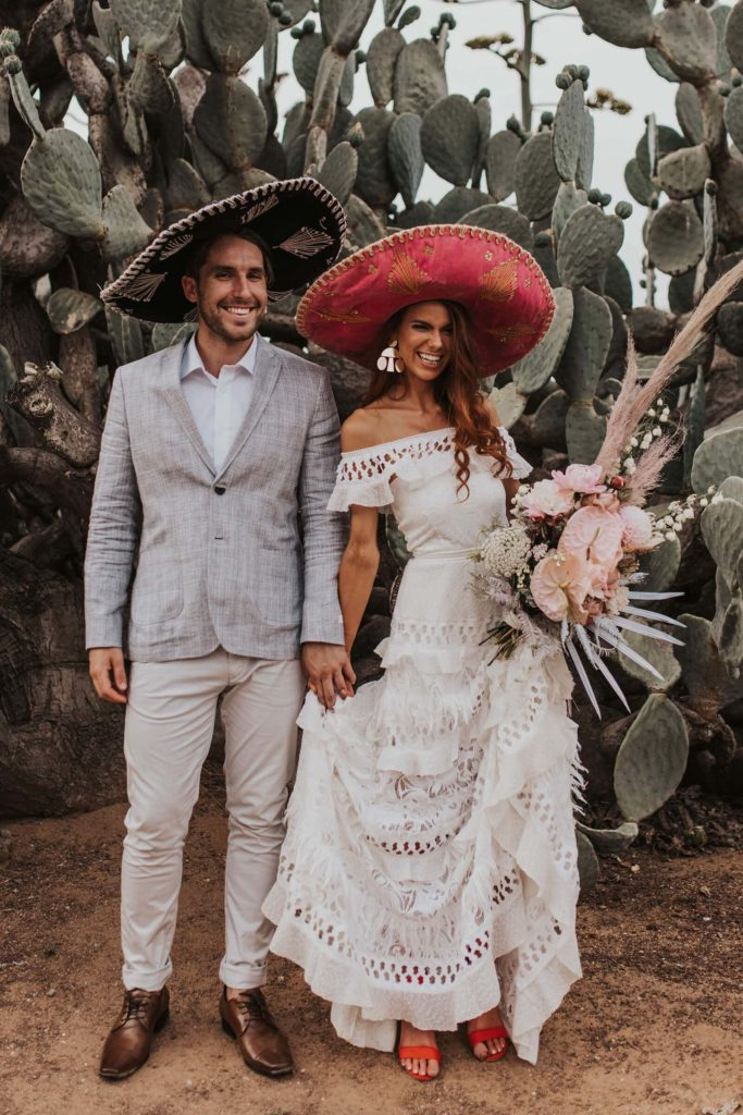 Brunette bride wearing Grace Loves Lace Coco Gown holding hands with groom wearing sombreros
