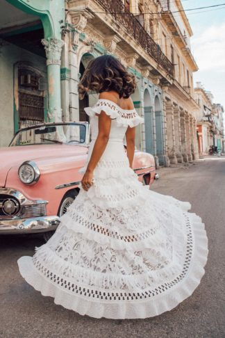 Back shot of bride wearing Grace Loves Lace Coco Gown twirling on street in front of pink classic car