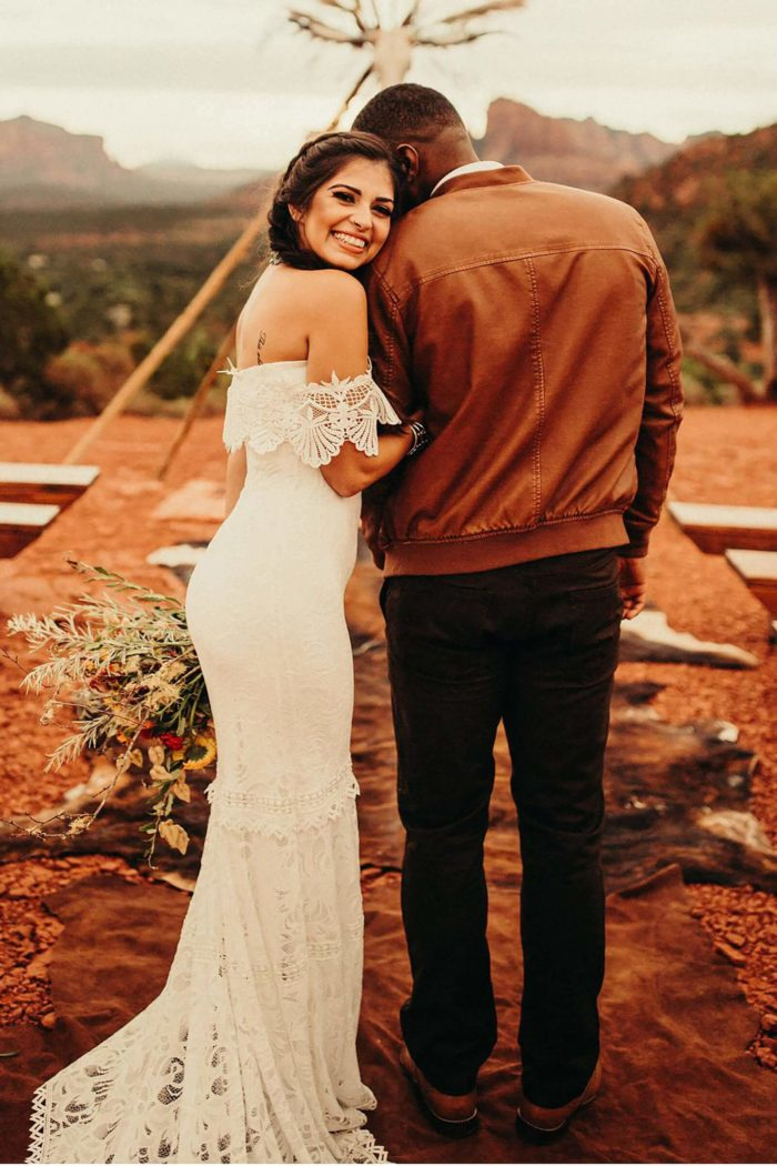 Brunette bride wearing Grace Loves Lace Cien Gown embracing groom