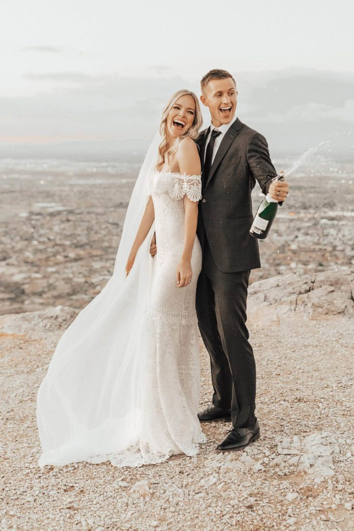 Blonde bride wearing Grace Loves Lace Cien Gown standing with groom holding champagne bottle