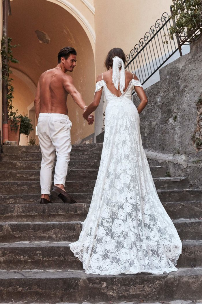 Back shot of bride wearing Grace Loves Lace Bonita Gown holding hands with shirtless man on stairs