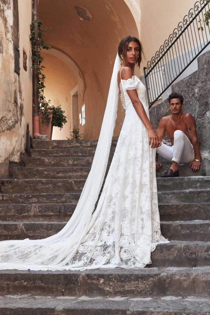 Side shot of bride wearing Grace Loves Lace Bonita Gown standing on stairs with shirtless man sitting down