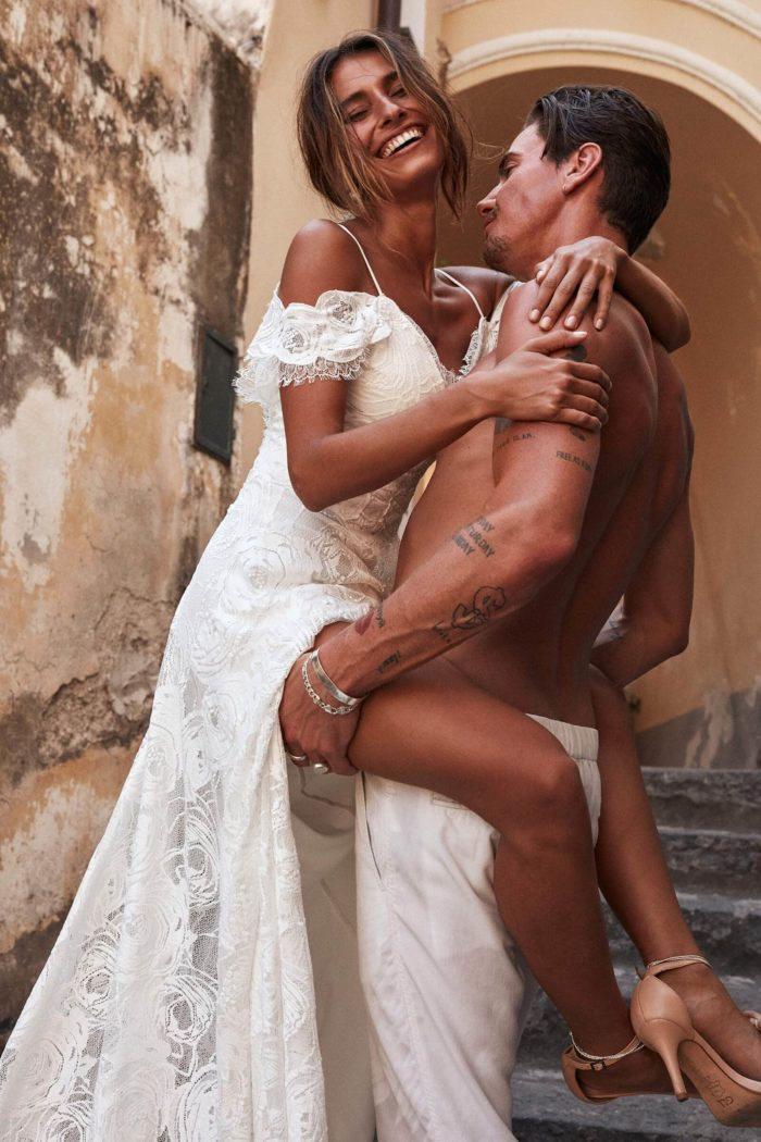 Side shot of bride wearing Grace Loves Lace Bonita Gown being held by shirtless man on stairs