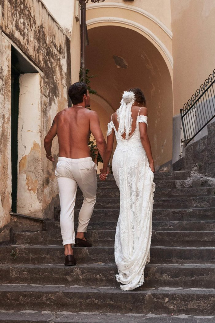 Back shot of bride wearing Grace Loves Lace Bonita Gown walking up stairs holding hands with shirtless man