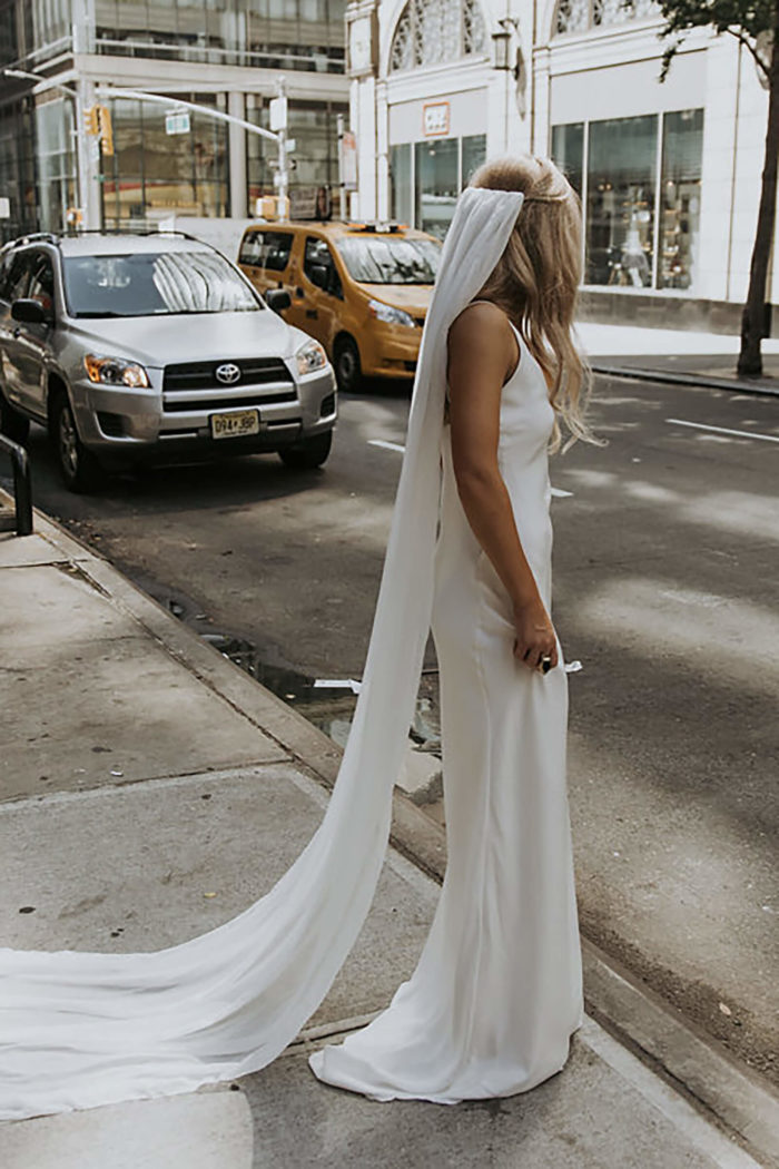 Back shot of bride wearing Grace Loves Lace Arlo Gown standing on street wearing veil holding skirt in hand