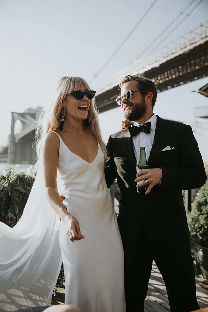Blonde bride wearing Grace Loves Lace Arlo Gown standing with groom wearing sunglasses