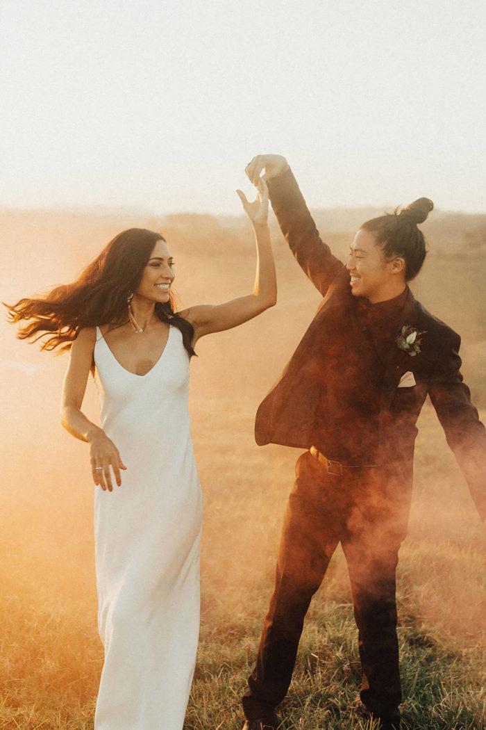 Brunette bride wearing Grace Loves Lace Arlo Gown dancing with groom in dusty field