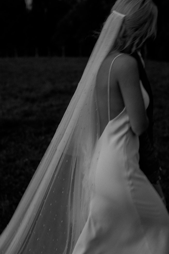 Black and white photo of bride wearing Grace Loves Lace Pearly Blusher Veil in a field, walking beside the groom