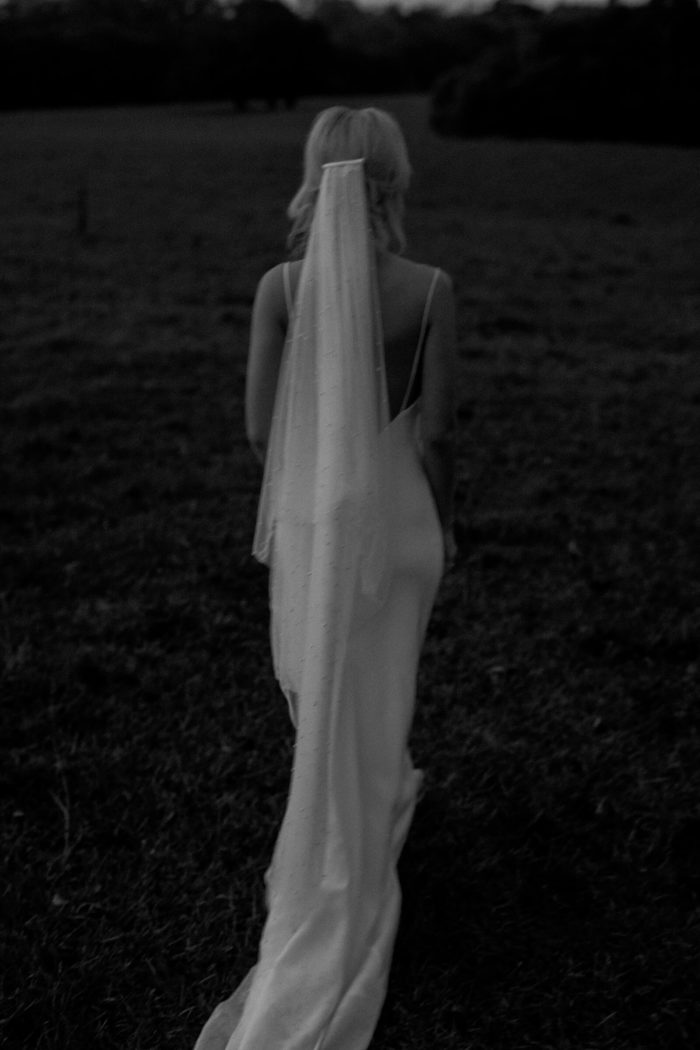 Black and white back shot of bride wearing Grace Loves Lace Pearly Blusher Veil in a field.