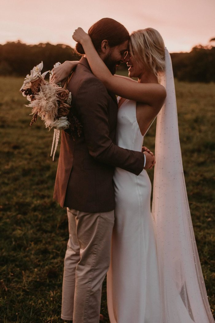 Bride wearing Grace Loves Lace Pearly Blusher Veil in a grassy field while embracing groom and laughing