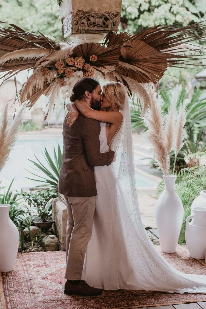 Bride wearing Grace Loves Lace Pearly Blusher Veil as she kisses her groom underneath a decorated pillar