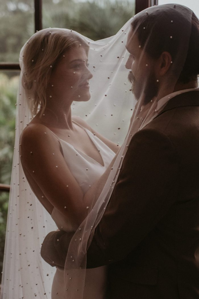 Bride wears Grace Loves Lace Pearly Blusher Veil while embracing the groom as they share the veil