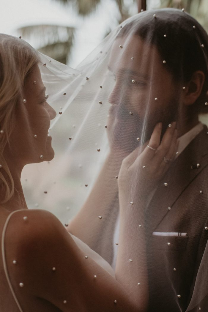 Close-up of bride wearing Grace Loves Lace Pearly Blusher Veil while caressing the groom's face