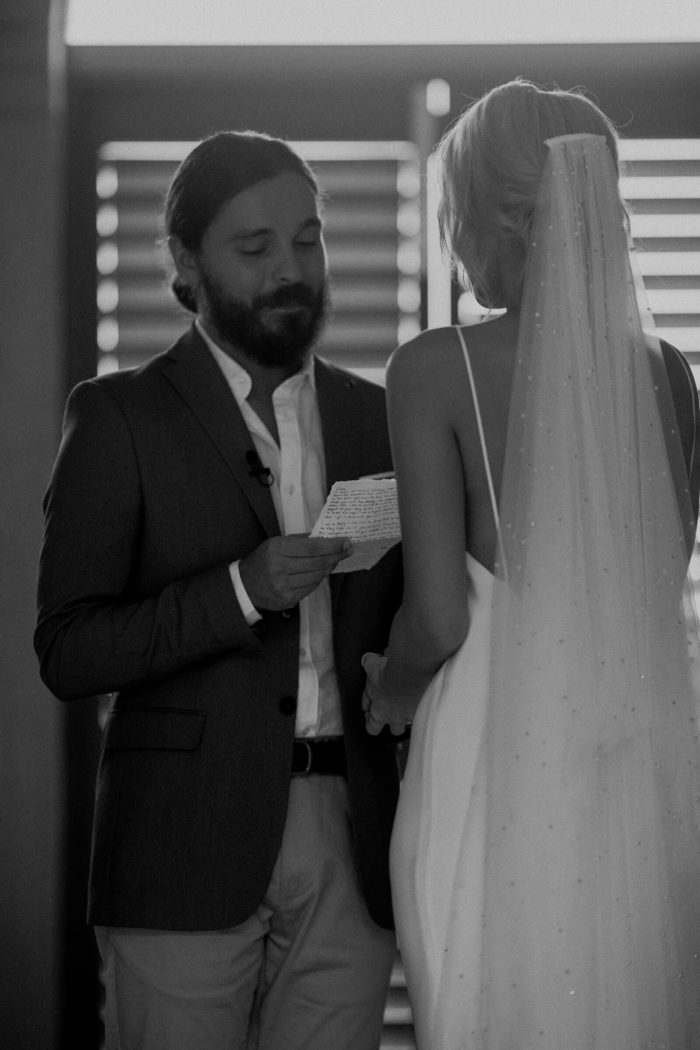 Black and white shot of bride wearing Grace Loves Lace Pearly Blusher Veil while holding hands with the groom as he says his vows