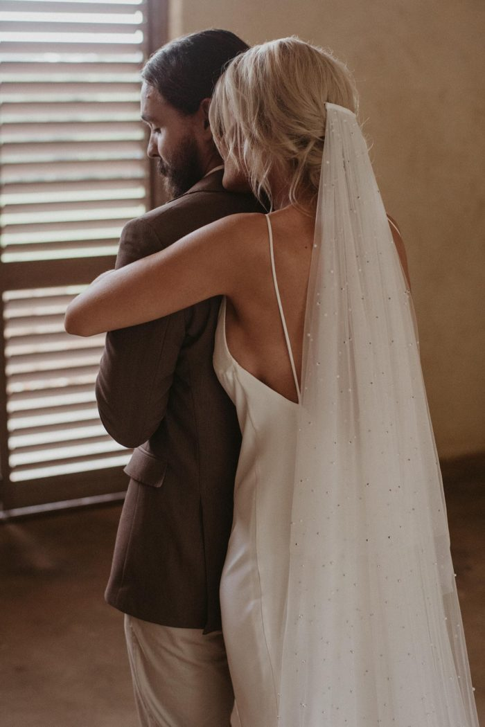 Bride wearing Grace Loves Lace Pearly Blusher Veil while embracing the groom from behind