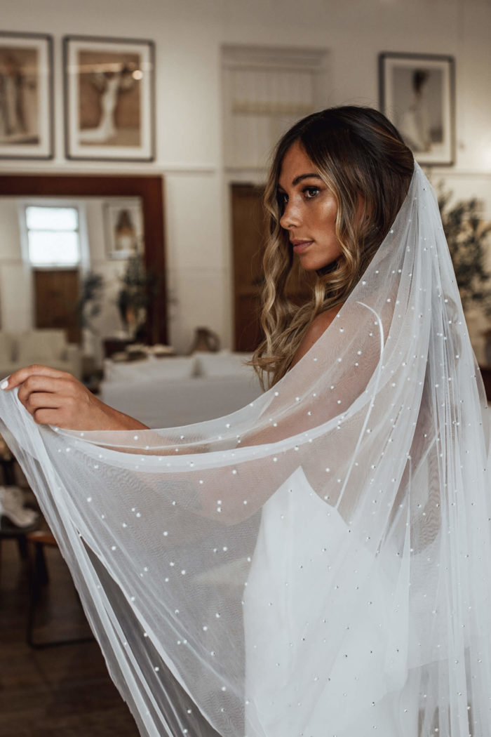 Bride wears Grace Loves Lace Pearly Blusher Veil, holding it up in one hand