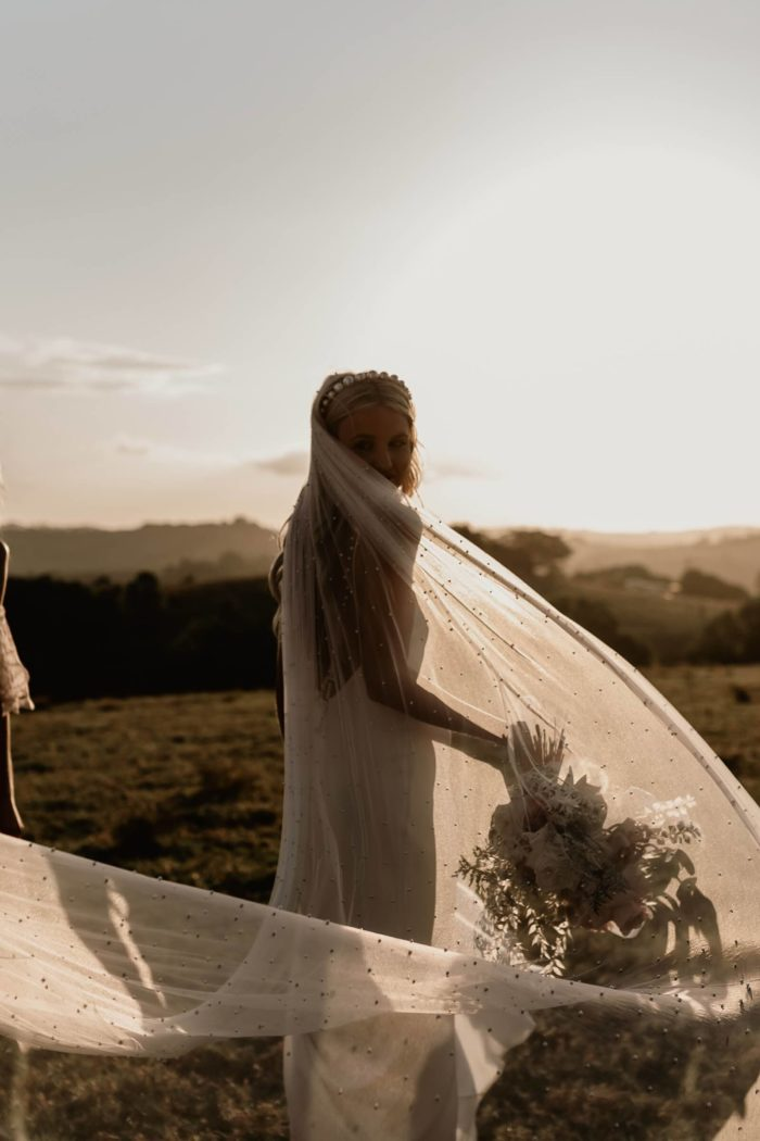 Bride looking back at camera wearing Grace Loves Lace Pearly Long Veil while holding flower bouquet in a grassy field