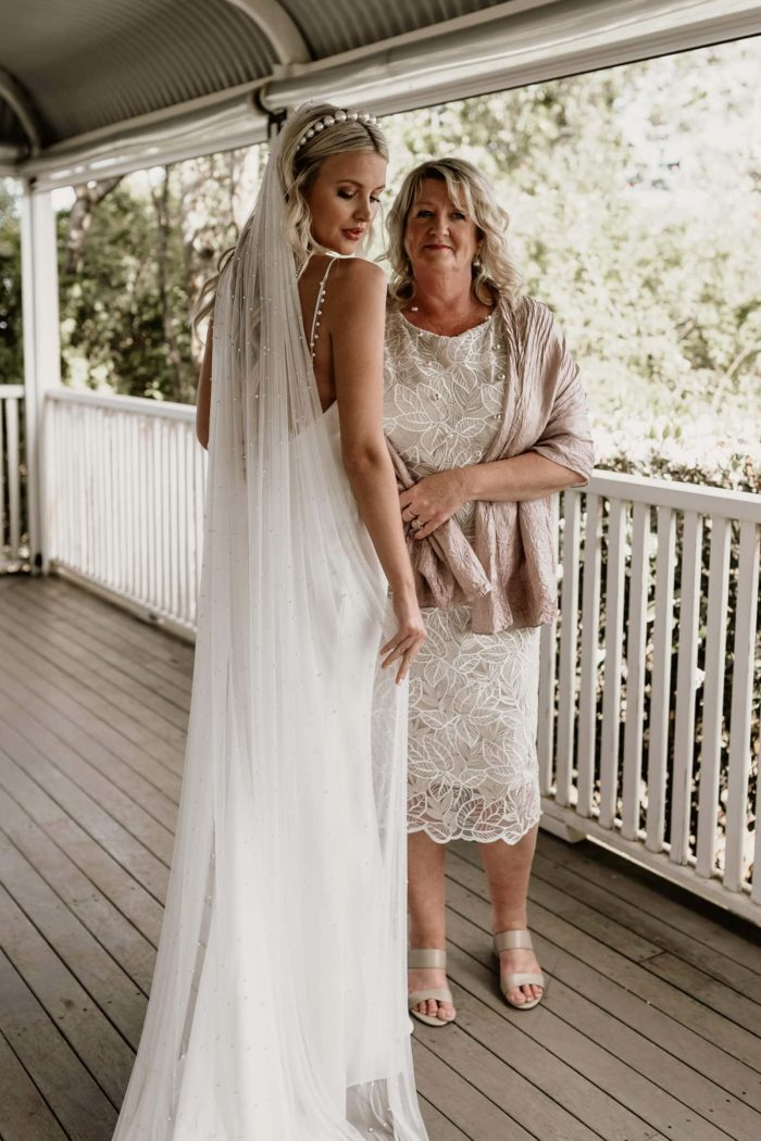 Back shot of bride wearing Grace Loves Lace Pearly Long Veil with Pearl headband standing next to an older woman