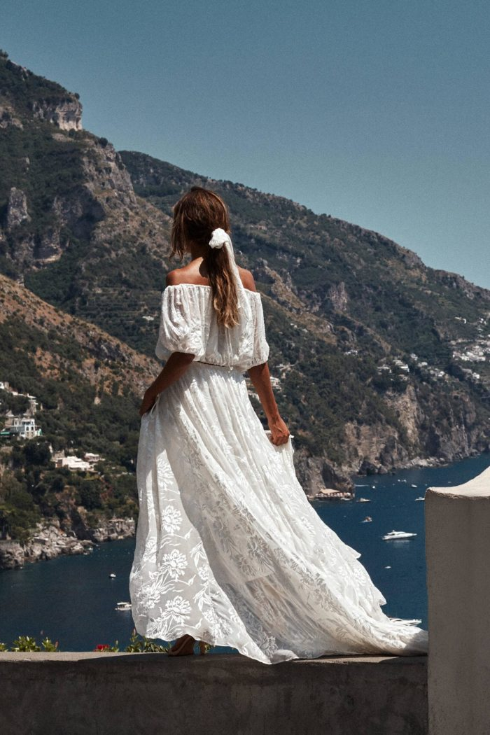 Bride wears Grace Loves Lace Loyola Pope Silk Scarf around her hair while standing on a ledge in front of the ocean