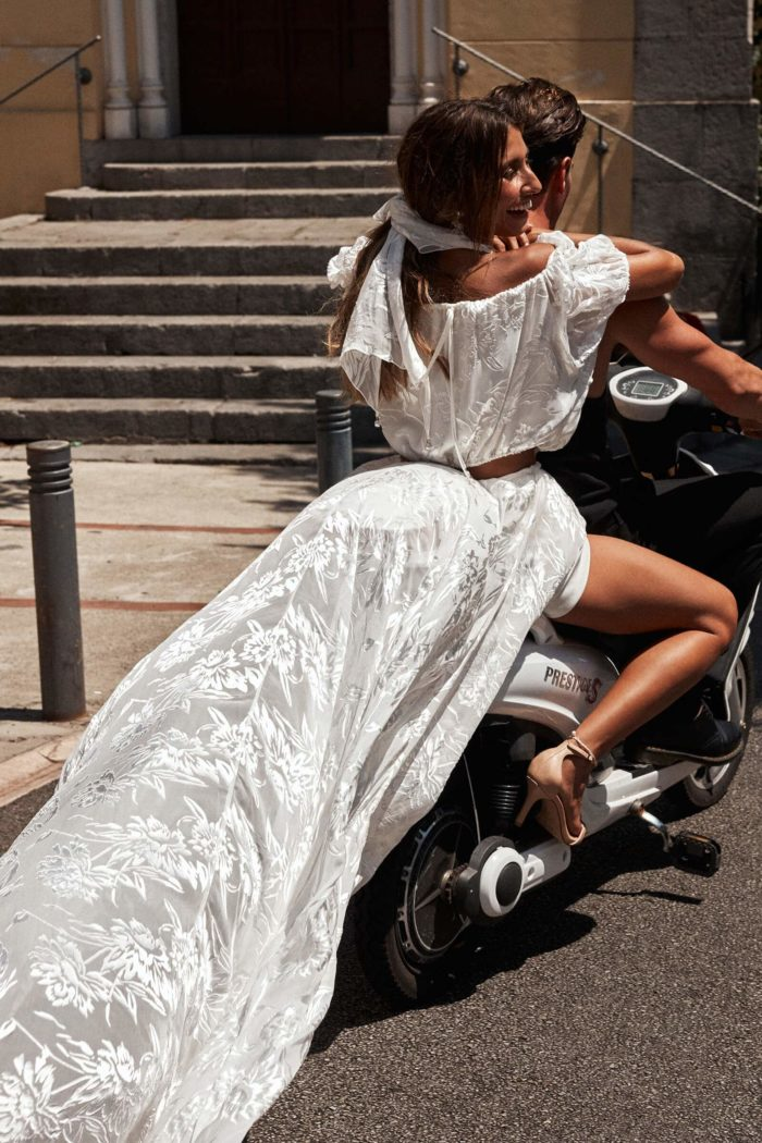 Bride wears Grace Loves Lace Loyola Pope Silk Scarf around her neck while sitting in the passenger seat of a motorbike behind a man