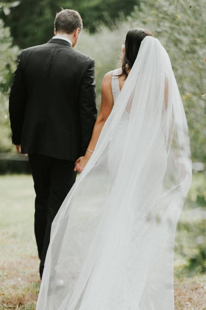 Bride wears Grace Loves Lace Henri Veil while holding hands with groom in a garden