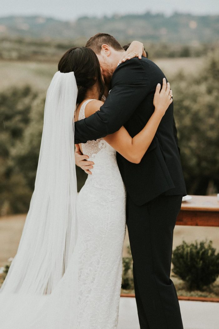 Bride wears Grace Loves Lace Henri Veil while embracing and kissing groom