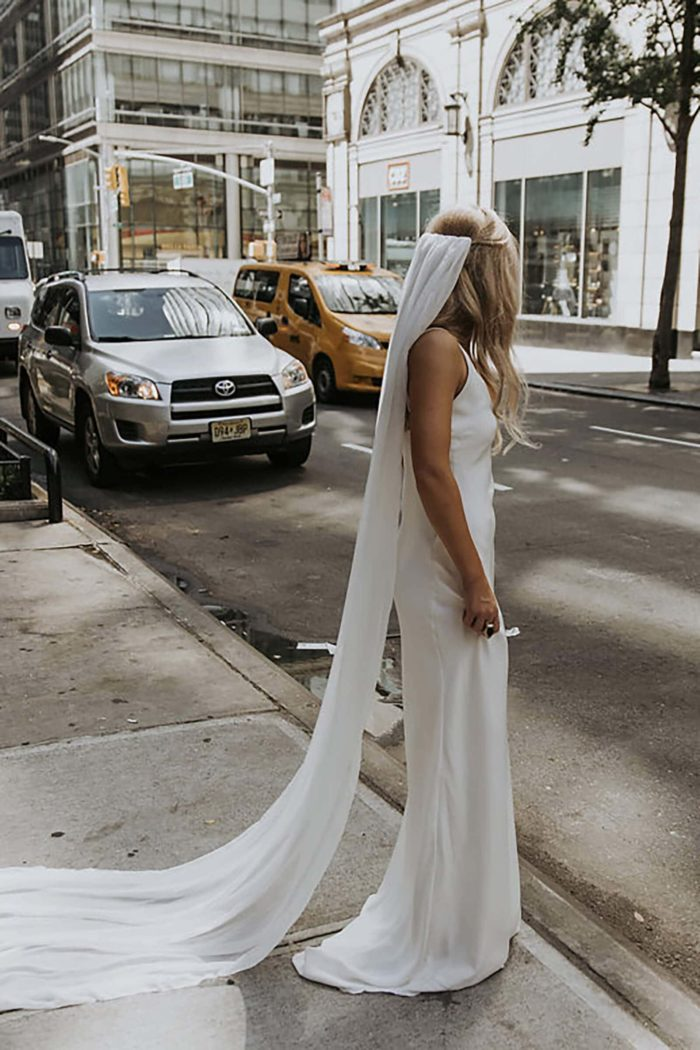 Bride wears Grace Loves Lace Gabriela Veil standing on street curb with cars behind her