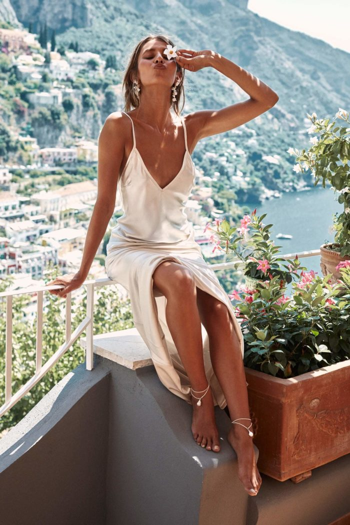 Brunette bridesmaid wearing Grace Loves Lace Farrow Slip Gown sitting on white railing holding a white flower above eye