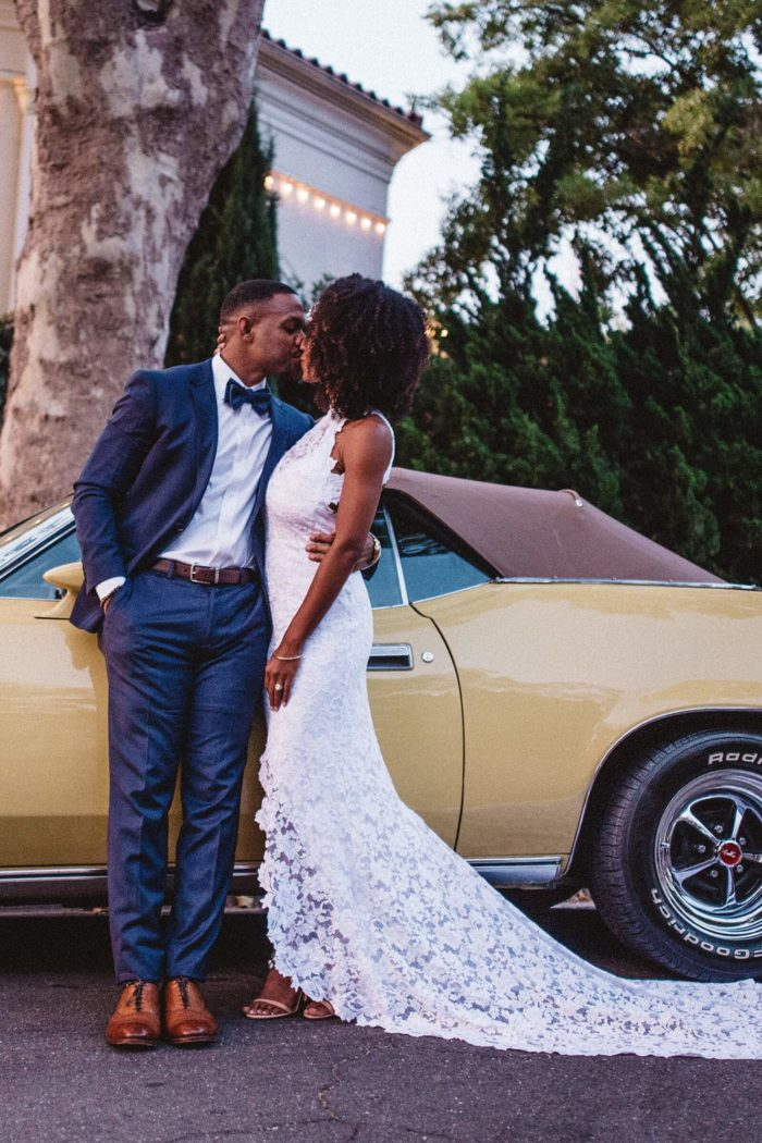 Bride wearing Grace Loves Lace Alexandra Gown kissing groom leaning against yellow car