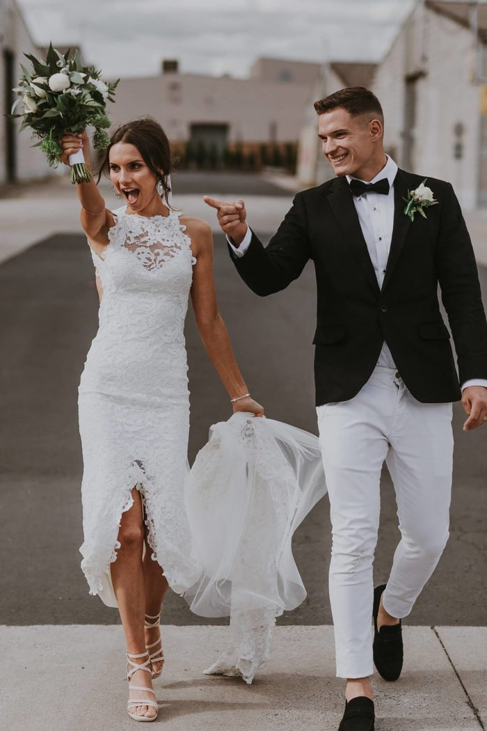 Bride wearing Grace Loves Lace Alexandra Gown walking with groom holding bouquet