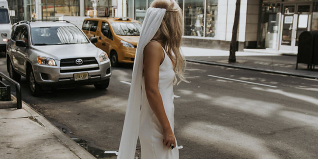 Bride standing in the streets of New York near a yellow taxi wearing the Gabriela veil and Arlo gown.