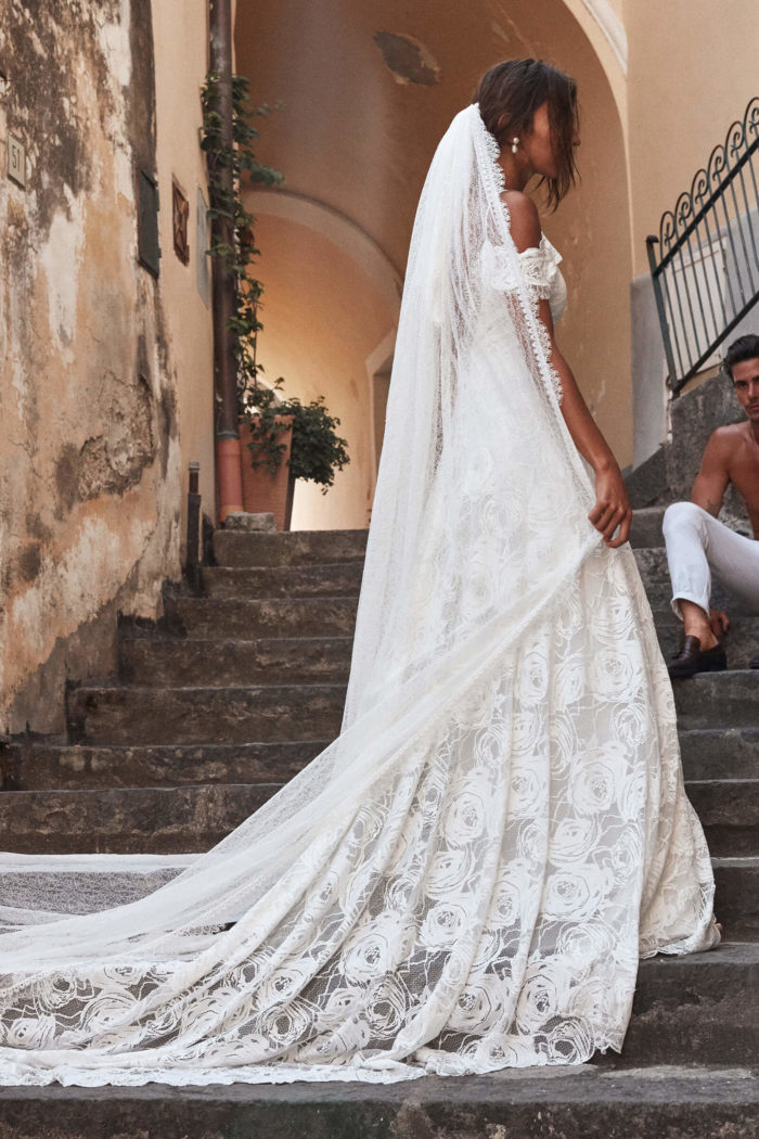 Bride wears Grace Loves Lace Chantilly Veil standing on stone staircase with shirtless man sitting behind her