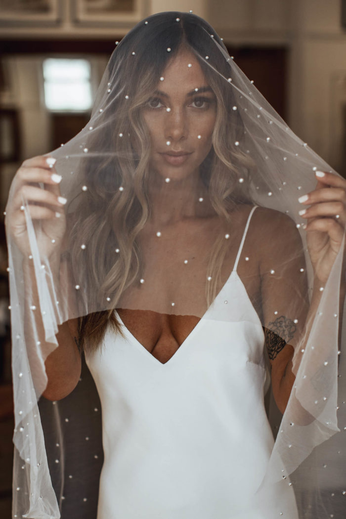 Bride holds Grace Loves Lace Pearly Blusher Veil over her face in her hands
