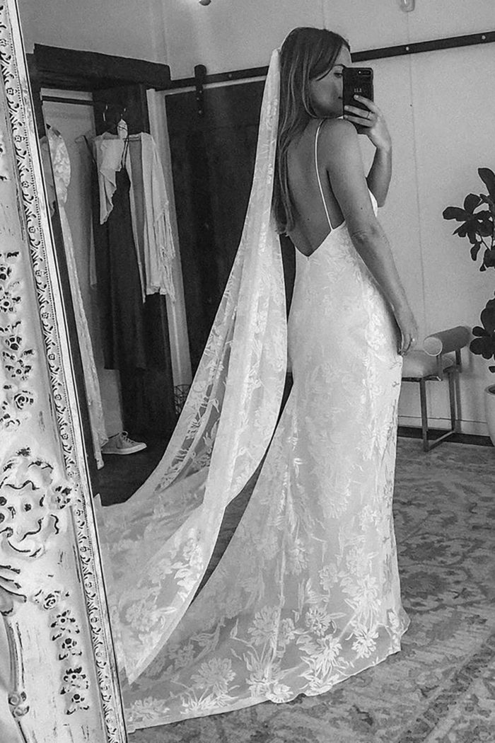 Black and white back shot of bride wearing Grace Loves Lace Loloya Veil taking photo in mirror with a phone