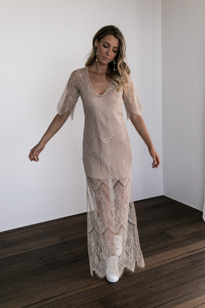 Bridesmaid wearing Grace Loves Lace Lace Maxi Dress in Champagne with white sneakers