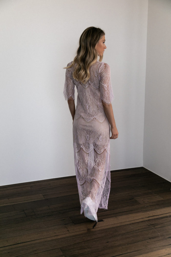 Back shot of bridesmaid wearing Grace Loves Lace Lace Maxi Dress in Amethyst with white sneakers