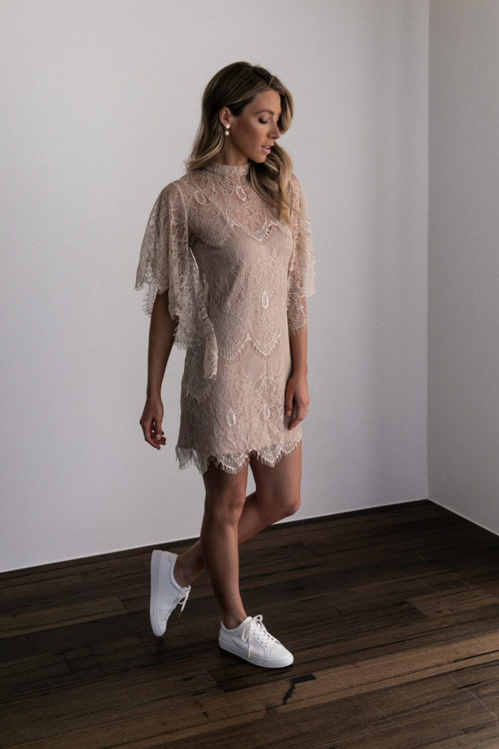 Bridesmaid wearing Grace Loves Lace High Neck Shift Dress in Champagne with white sneakers
