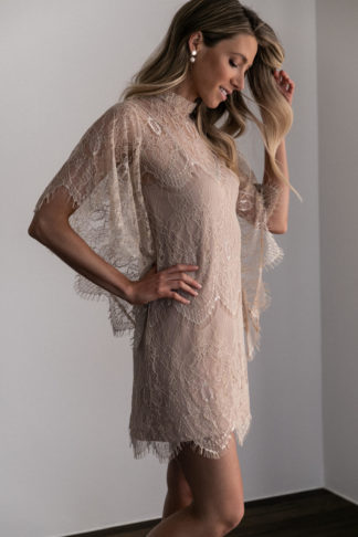 Bridesmaid wearing Grace Loves Lace High Neck Shift Dress in Champagne with hand on hair